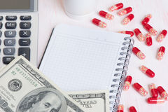 消耗大的医学 药片和货币 库存图片