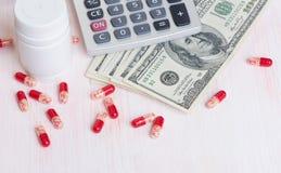 消耗大的医学 药片和货币 免版税库存图片