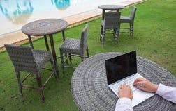 消遣企业家 有膝上型计算机的人在海滩工作的早晨 免版税图库摄影