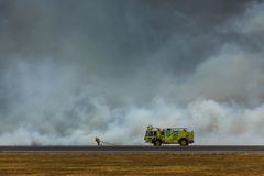 消防员作战关闭圣萨尔瓦多国际机场的灌丛火 免版税库存图片