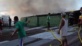 消防员和志愿者在屋顶被投入的火聚集使用灭火水龙带在毁坏内部简陋小木屋房子的房子火期间 股票视频
