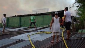 消防员和志愿者在屋顶被投入的火聚集使用灭火水龙带在毁坏内部简陋小木屋房子的房子火期间 股票录像