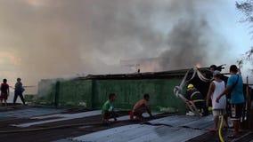 消防员和志愿者在屋顶被投入的火聚集使用灭火水龙带在毁坏内部简陋小木屋房子的房子火期间 影视素材