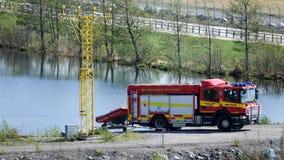 消防员在一个小湖使一条肋骨小船下水 库存照片