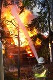 消防员在房子的用途水火的 库存图片