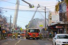 消防员在爆炸以后浸入火焰在R的一家便利商店 免版税库存图片