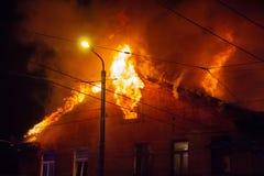 消防员指挥在灼烧的房子的水小河 大厦在充分的火焰状地域和得到fl的控制的消防队员战斗 免版税库存照片