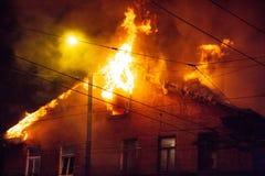 消防员指挥在灼烧的房子的水小河 大厦在充分的火焰状地域和得到fl的控制的消防队员战斗 免版税图库摄影