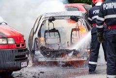 消防员熄灭在火的汽车 库存图片