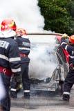 消防员熄灭在火的汽车 免版税库存照片