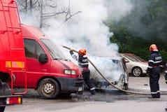 消防员熄灭在火的汽车 免版税库存图片