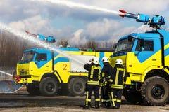 消防员钻子,水溢出燃烧区域 库存图片