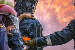消防实习生队熄灭与水消防栓的巨大的火 库存照片