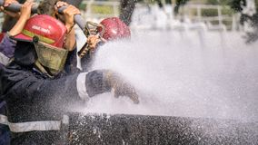 消防实习生队熄灭巨大的火用水 库存图片
