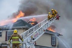 消防队员争斗燃烧的房子火 库存图片