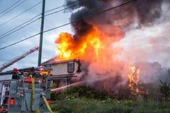 消防队员争斗燃烧的房子火 免版税库存照片