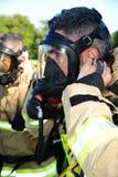 消防队员准备他的呼吸器官面具在火场面 图库摄影