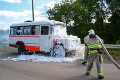 消防队员在一辆灼烧的公共汽车上熄灭火 库存图片