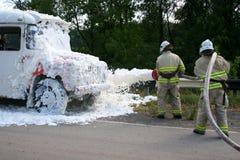 消防队员在一辆灼烧的公共汽车上熄灭火 免版税库存照片