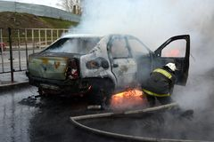 消防队员在俄罗斯熄灭一辆灼烧的汽车 免版税库存照片