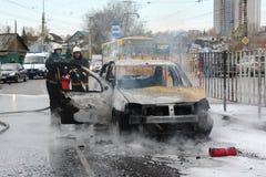 消防队员在俄罗斯熄灭一辆灼烧的汽车 库存图片
