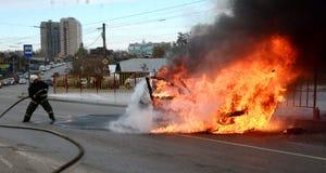 消防队员在俄罗斯熄灭一辆灼烧的汽车 免版税库存图片