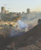 消防队员在城市飞行在火的被投下的泡沫 免版税库存图片