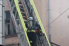 消防队员在救火梯起来 库存图片
