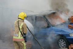 消防队员战斗的汽车火 免版税库存图片