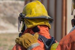 消防队员手在火投入了第一个人肩膀信号的 免版税库存照片