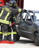消防队员打开汽车的门有的强有力的剪 免版税库存照片