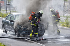 消防队员投入一辆灼烧的汽车 免版税库存图片