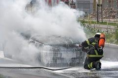 消防队员投入一辆灼烧的汽车 库存图片