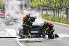 消防队员投入一辆灼烧的汽车 免版税图库摄影