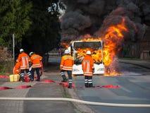 消防队员熄灭一辆灼烧的公共汽车 免版税库存照片