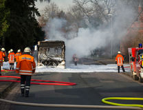消防队员熄灭一辆灼烧的公共汽车 免版税库存图片