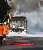 消防队员熄灭一辆灼烧的公共汽车 免版税图库摄影