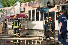 消防队员熄灭大火在市场上 库存照片