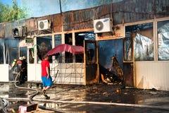 消防队员熄灭大火在市场上 免版税库存图片
