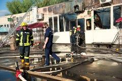 消防队员熄灭大火在市场上 库存图片