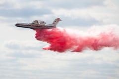 消防队员航空器BE-200投掷水 免版税库存照片