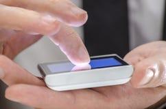 涉及电话屏幕的手指的详细资料 库存照片