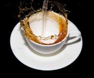 涌入一个茶碟的茶与在黑背景飞溅 免版税图库摄影