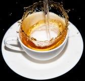 涌入一个茶碟的茶与在黑背景飞溅 库存照片