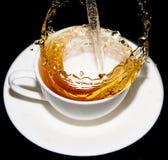涌入一个茶碟的茶与在黑背景飞溅 库存图片