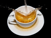涌入一个茶碟的茶与在黑背景飞溅 免版税库存图片