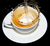 涌入一个茶碟的茶与在黑背景飞溅 图库摄影