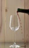 涌入一个玻璃瓶的红葡萄酒与一块精采玻璃的红葡萄酒在玻璃立场的木背景 免版税库存图片
