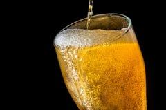 涌入一块玻璃用啤酒和泡沫的啤酒小河隔绝在黑背景,特写镜头纹理 免版税库存图片