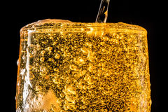 涌入一块玻璃用啤酒和泡沫的啤酒小河隔绝在黑背景,特写镜头纹理 免版税图库摄影